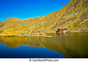 a brown wooden house on glacier lake with very clear mountain water, Balea Lac, Romania