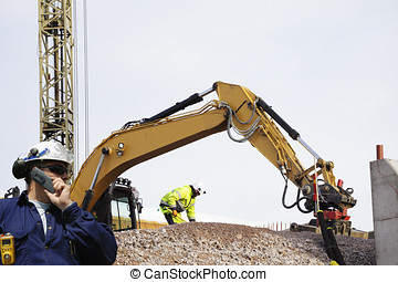bulldozer in action - bulldozer, digger and workers in...