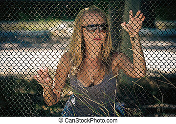 the beautiful girl wearing spectacles behind a lattice