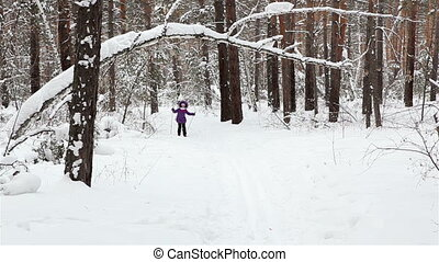 little girl is skiing in the forest