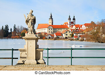 Telc chateau and church above a frozen pond and statue of...