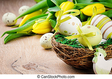 Easter eggs in holiday setting with yellow tulips