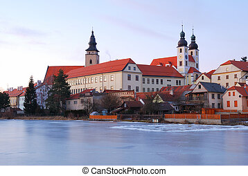 Telc historic chateau and church towers in sunset light