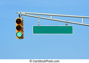 Green traffic signal light with sign on blue sky