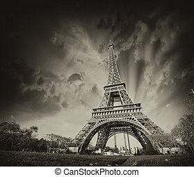 Wonderful view of Eiffel Tower in Paris. La Tour Eiffel with sunset sky and meadows.