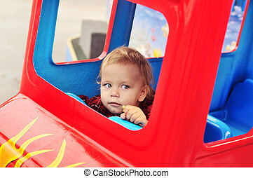baby in theme park - baby girl driving a train in theme park...