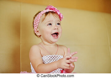 smiling baby girl with flower on the head in soft selective...