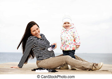 pregnant mother with daughter near the sea