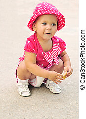 funny baby girl wearing spotted clothing eating cakes...