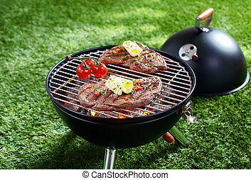 Cooking steak on a barbecue - High angle view of two...