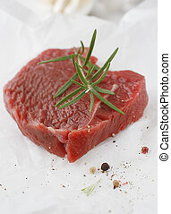 Portion of healthy lean steak topped with fresh rosemary as...