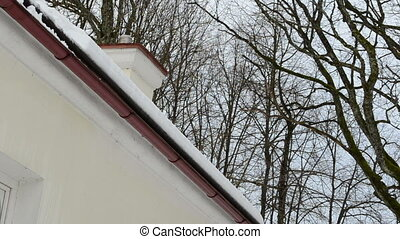 slope roof snow fall - closeup of slope roof corner and snow...