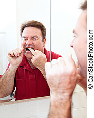 Flossing Teeth In Bathroom Mirror - Man flossing his teeth...