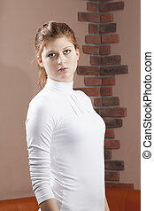 Earnest woman in white shirt standing against a wall