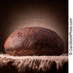 Loaf of rye bread on rustic background