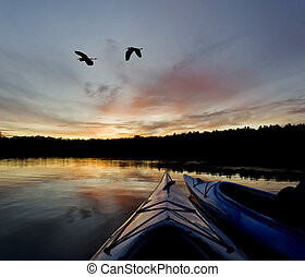 Wilderness Lake Sunset - Two kayakers enjoying the sunset on...