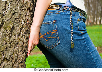 overhead part of jeans, womanish hand and tree