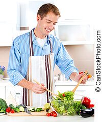 Young Man Cooking. Healthy food. Vegetable Salad