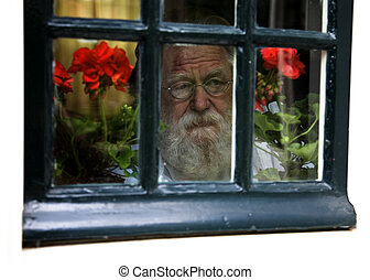 Old man with grey beard looking through the window