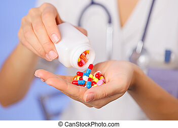 Pills, tablets and drugs pouring from bottle in doctor's...