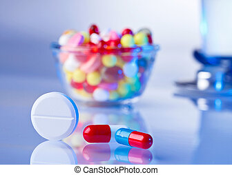 Pills and tablets macro still life on white blue, medical therapeutic concept