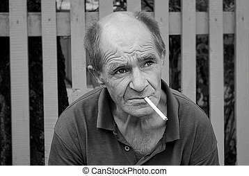 despair - Old man drunkard sitting near the fence, smoking a...