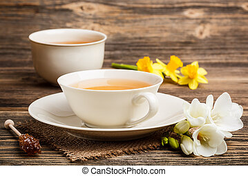 Cup of black tea with freesia and sugar stick