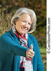 Senior woman holding thumbs up