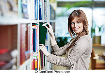 young student selecting book in library - young college...