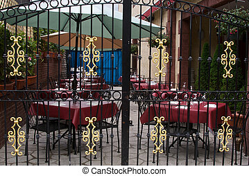 outdoor cafe - beautiful outdoor cafe behind ornate gate in...