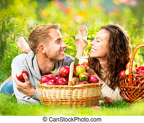 Couple Relaxing on the Grass and Eating Apples in Autumn Garden