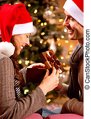 Christmas Scene. Happy Couple with Christmas Gift at Home