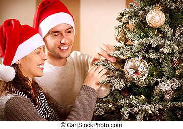 Happy Couple Decorating Christmas Tree in their Home