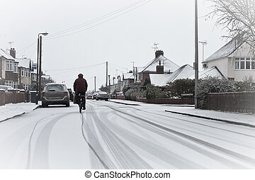Cyclist in the snow - A cyclist on a snowy residential raod...