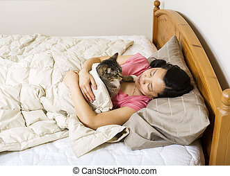 Mature woman looking at her cat while trying to sleep -...