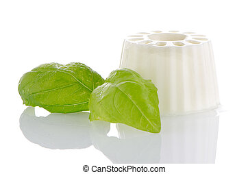 White fresh cheese with fresh basil leaves on white...