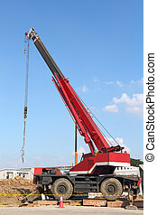 Red automobile crane against blue sky