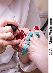 Pedicure - Woman foot in chiropodist hands at pedicure...