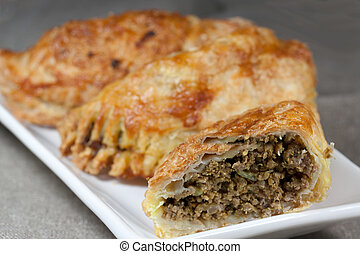pasties filled with minced meat on a white plate with beige...