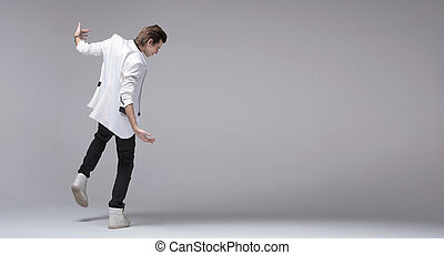 Handsome boy with jacket dancing alone