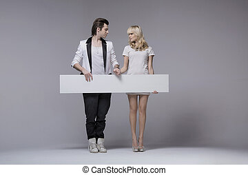 Picture presenting attractive couple with board