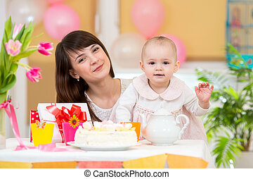 Little girl and mother celebrate birthday holiday. Focus at baby.