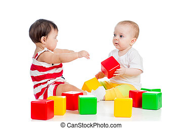 two babies or kids playing together with color toys - two...