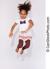 Portrait of Young African American girl jumping - Portrait...