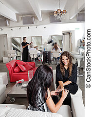 Woman Having Manicure At Parlor - Young woman having...