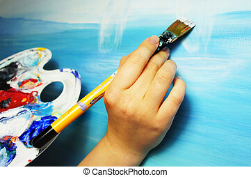 Artists hand with paintbrush painting the picture...