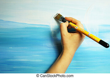 Artist?s hand with paintbrush painting the picture