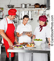 Chefs Using Digital Computer In Kitchen - Chefs looking for...