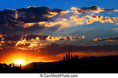 sunrise over mountains - clouds on bright blue sky over...