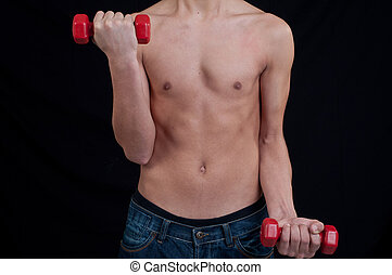 Fit young man exercising with dumbbell on black background